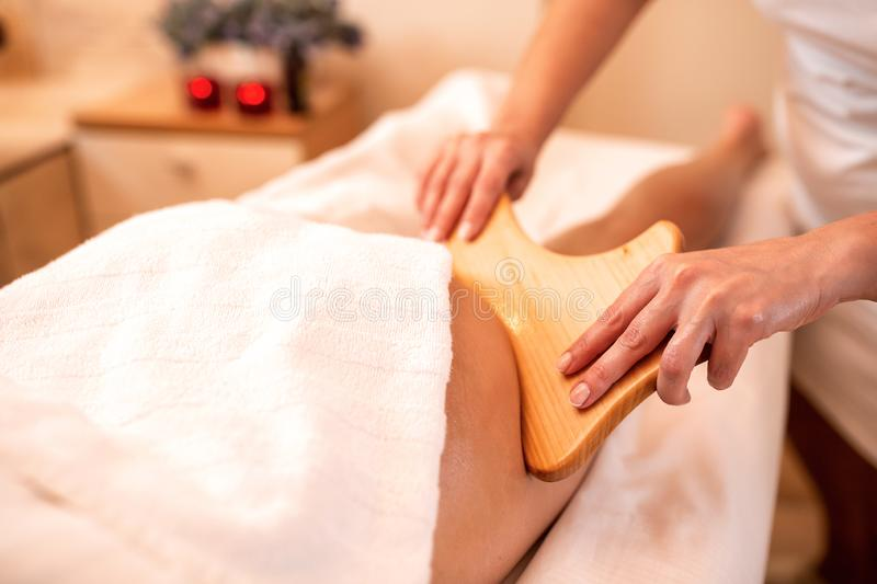 Masseuse holding a hand held wooden massage tool. Anti-cellulite massage stock image
