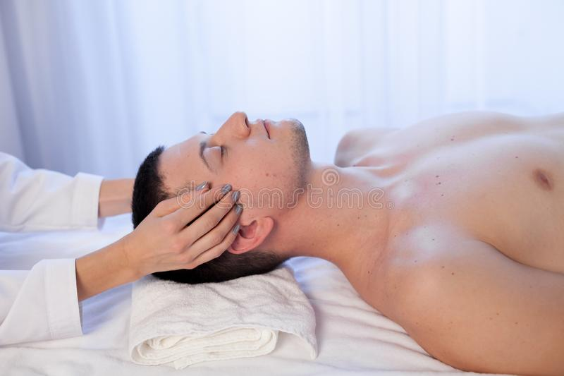 Masseuse makes a therapeutic massage of the head and neck man Spa stock image