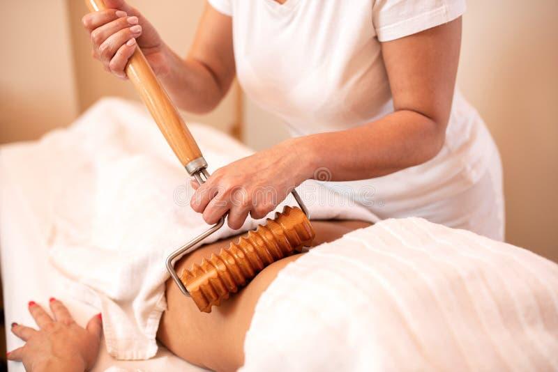 Masseuse massage hennes klients magområde royaltyfria bilder