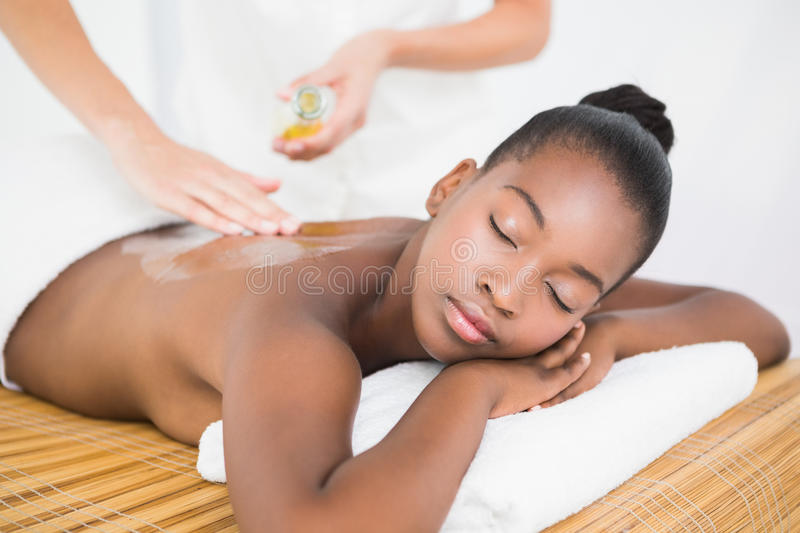 Masseuse pouring massage oil on a pretty woman back stock image
