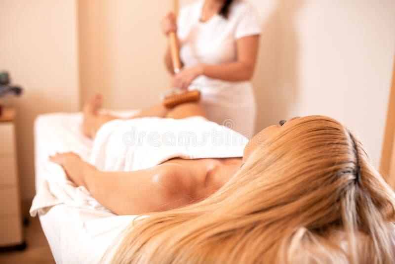 Masseuse som håller en förlängd handtagsrulle för massage av anti-cellulit royaltyfri fotografi