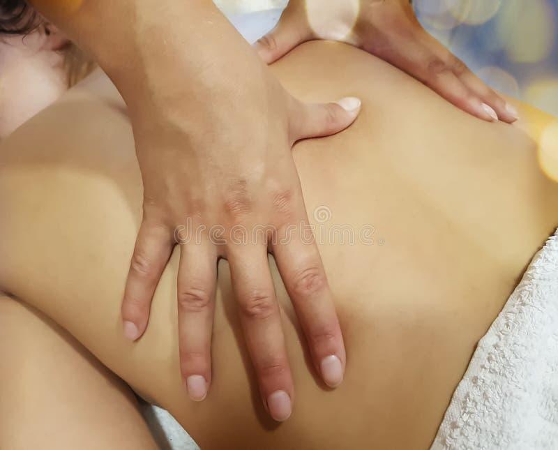 Massez le patient en bonne santé de plaisir de salon de thérapeute de mode de vie de beauté arrière de fille, procédure de statio image libre de droits