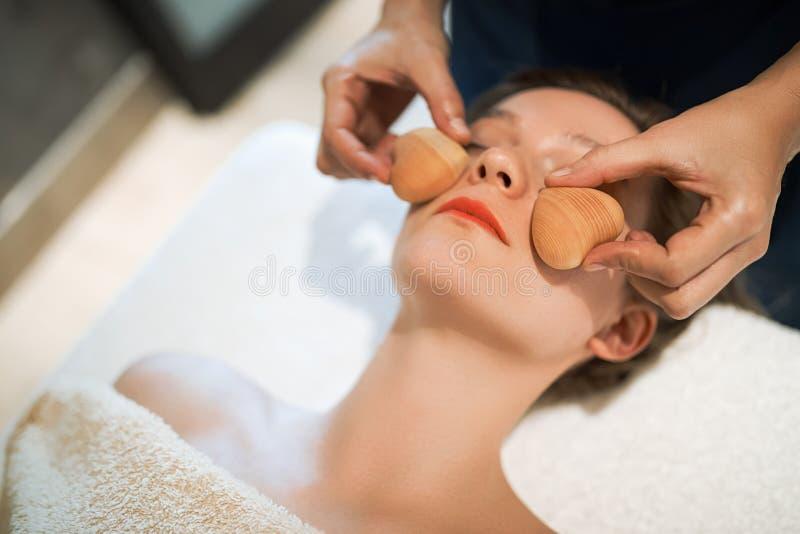 Massez le thérapeute à l'aide de l'outil en bois pour masser le patient photo stock
