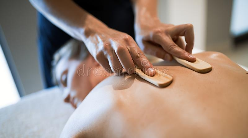 Massez le thérapeute à l'aide de l'outil en bois pour masser le patient photographie stock