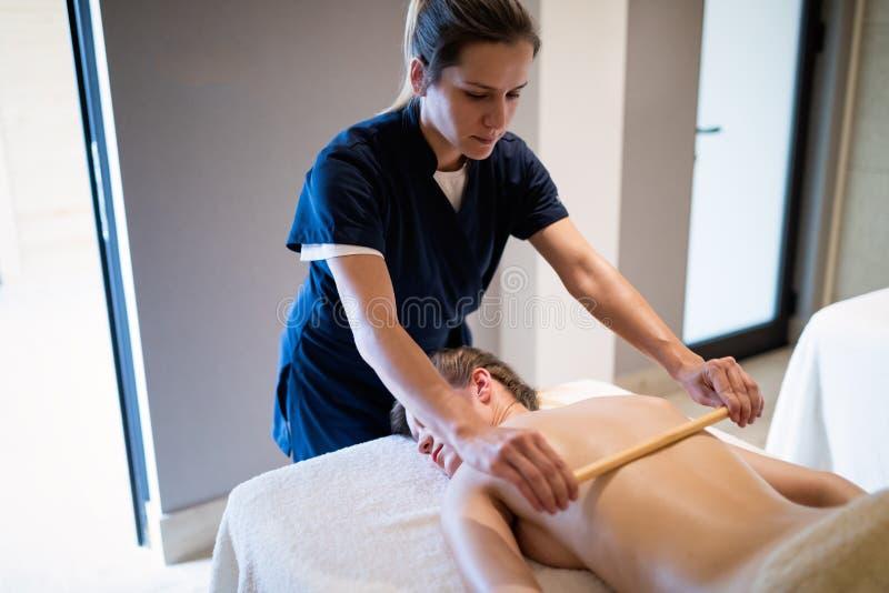 Massez le thérapeute à l'aide de l'outil en bois pour masser le patient photos stock