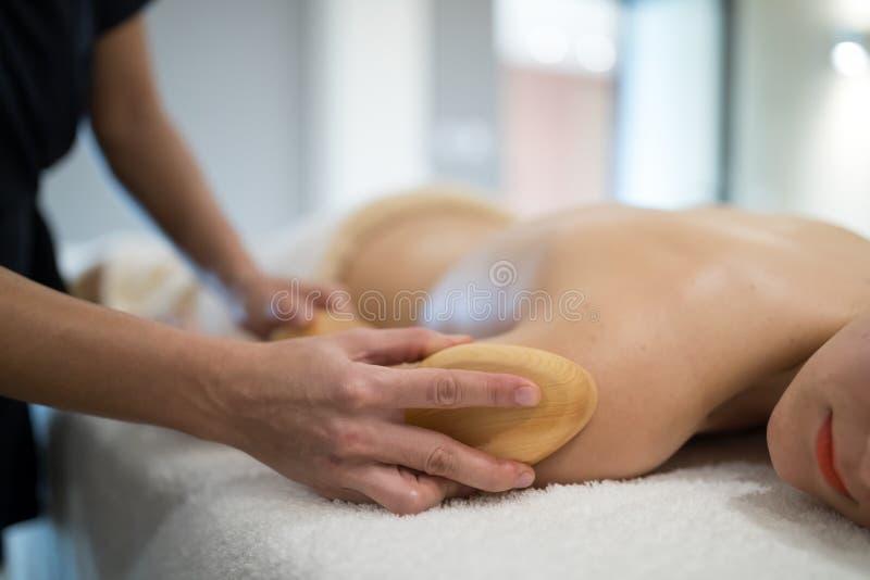 Massez le thérapeute à l'aide de l'outil en bois pour masser le patient photo libre de droits