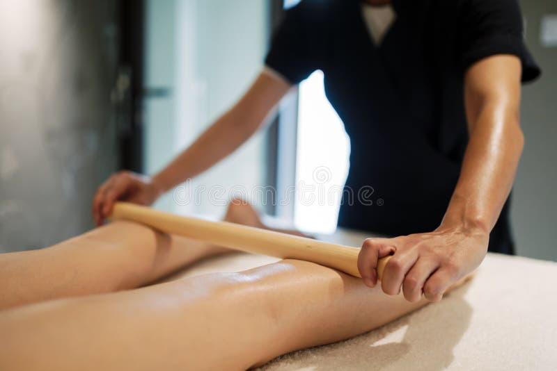 Massez le thérapeute à l'aide de l'outil en bois pour masser le patient images libres de droits