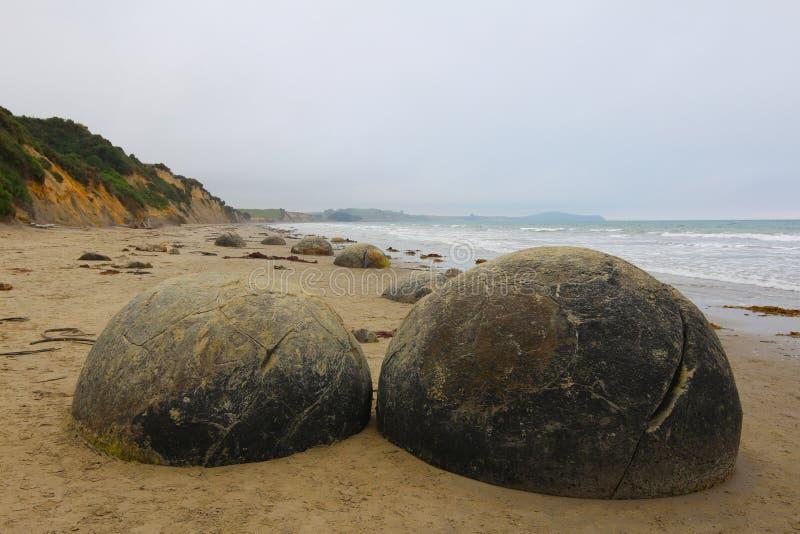 Massi di Moeraki in spiaggia di Koekohe sulla costa Wave tagliata di Otago della Nuova Zelanda immagini stock