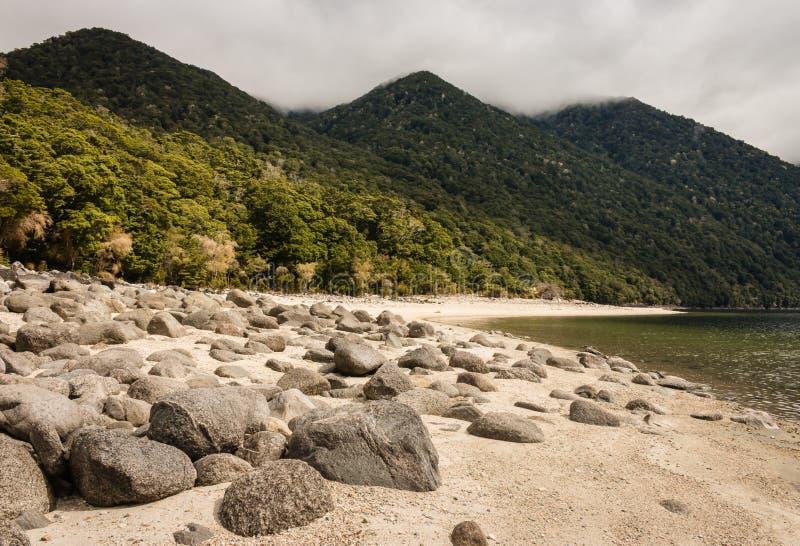 Massi sulla spiaggia di sabbia bianca nel lago Manapouri fotografie stock