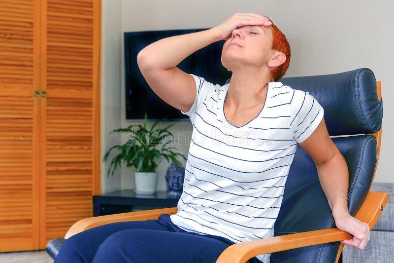 Massieren Sie seine Tempel Eine Frau, die unter Kopfschmerzen leidet Gesundheitsprobleme, Frau, die ihren Kopf mit ihrer Hand häl lizenzfreies stockbild