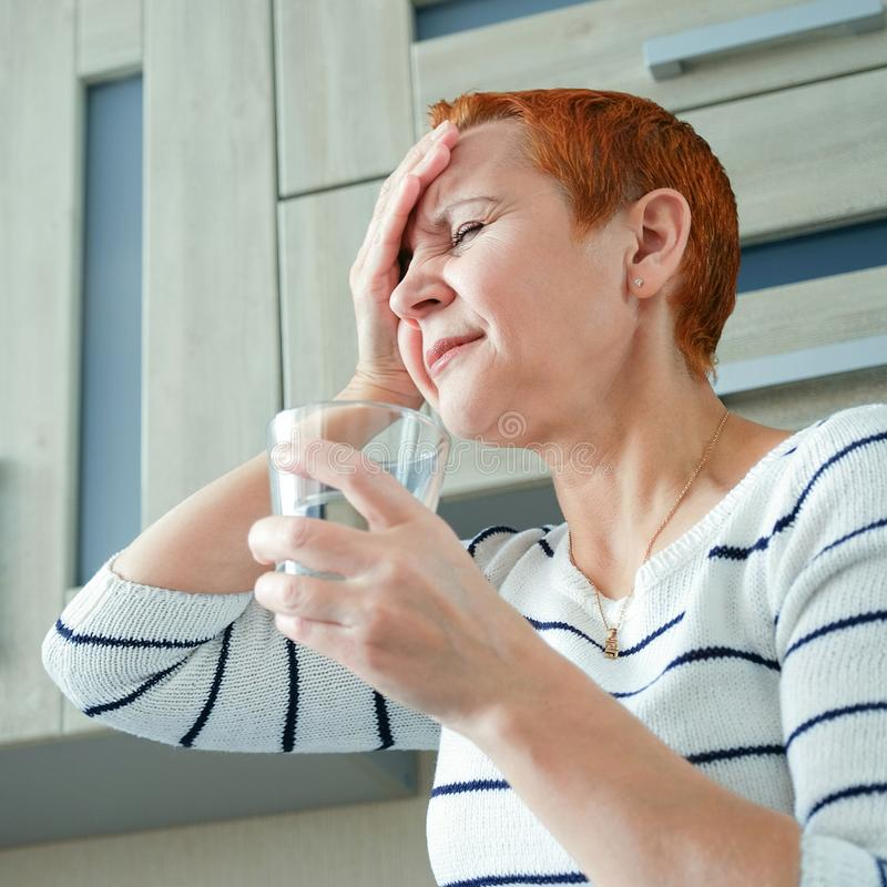 Massieren Sie seine Tempel Eine Frau, die unter Kopfschmerzen leidet Gesundheitsprobleme, Frau, die ihren Kopf mit ihrer Hand häl stockbilder