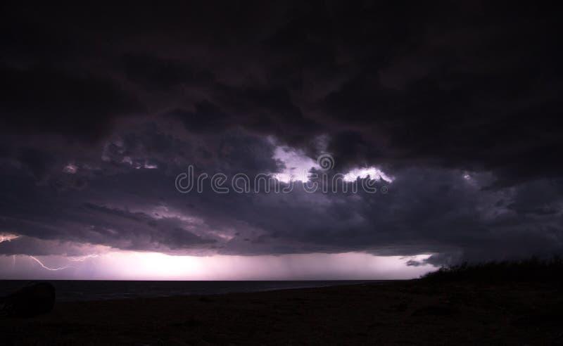 Massiv åskstorm med svart moln över havet och ljus vid horisonten royaltyfria bilder