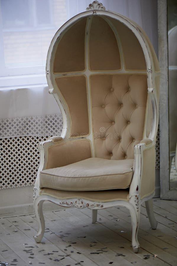 Massiv gammal stol med ljus tygstoppning och hög stängd baksida royaltyfri foto