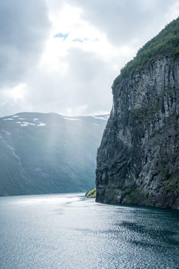 Massiv geirangerfjord för vertikal bild i Norge som ses från ett kryssningskepp med ljust skina till och med molnen royaltyfri bild