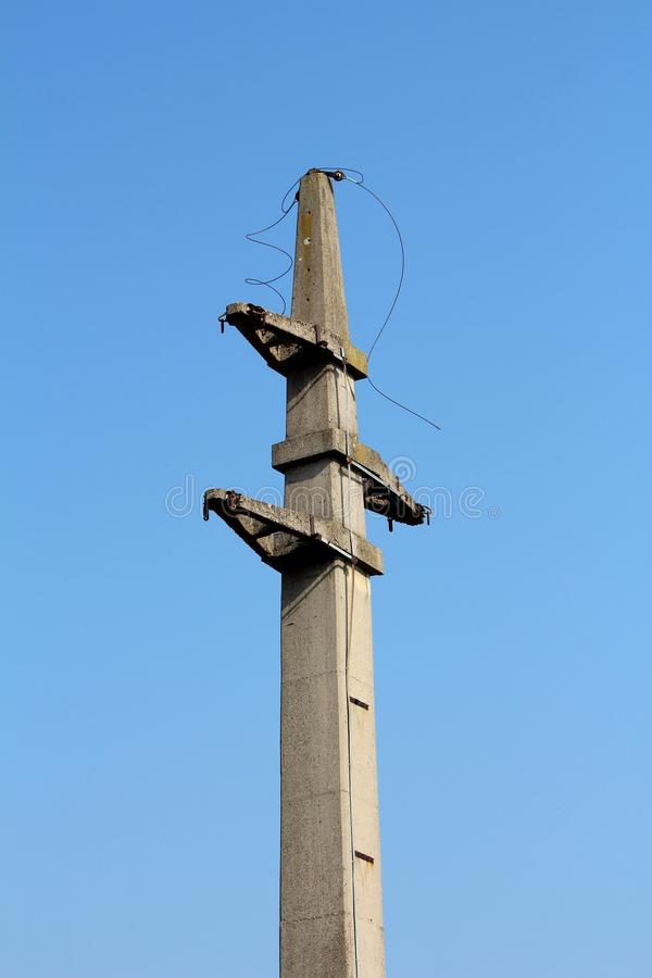 Massiv konkret elektrisk nytto- pol med klippta elektriska trådar som hänger från överkant arkivbild