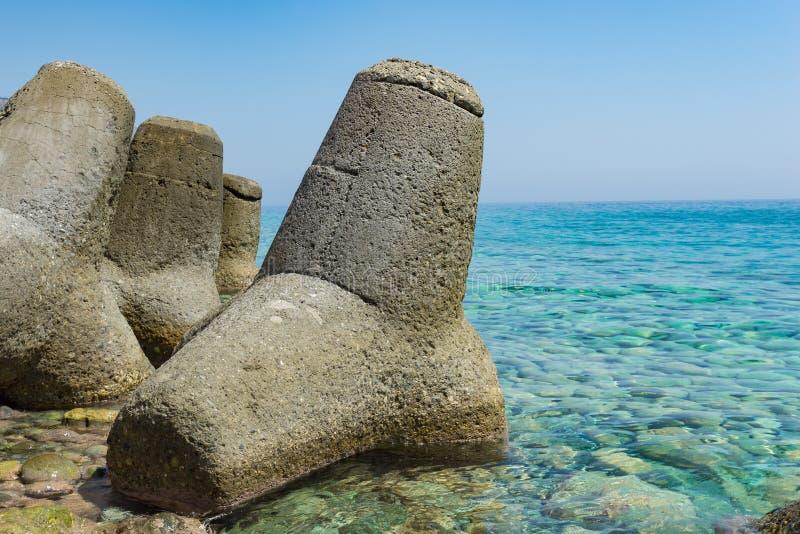 Massiv konkret tetrapodsform i det gröna vattenhavet, Grekland royaltyfri bild