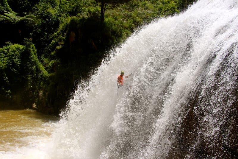 Massiv vattenfall för manliga abseils arkivfoton