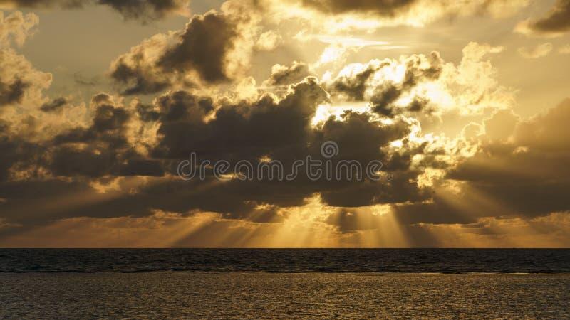 Massiva solstrålar under soluppgång över uddebedrövelsen Austalia arkivfoton