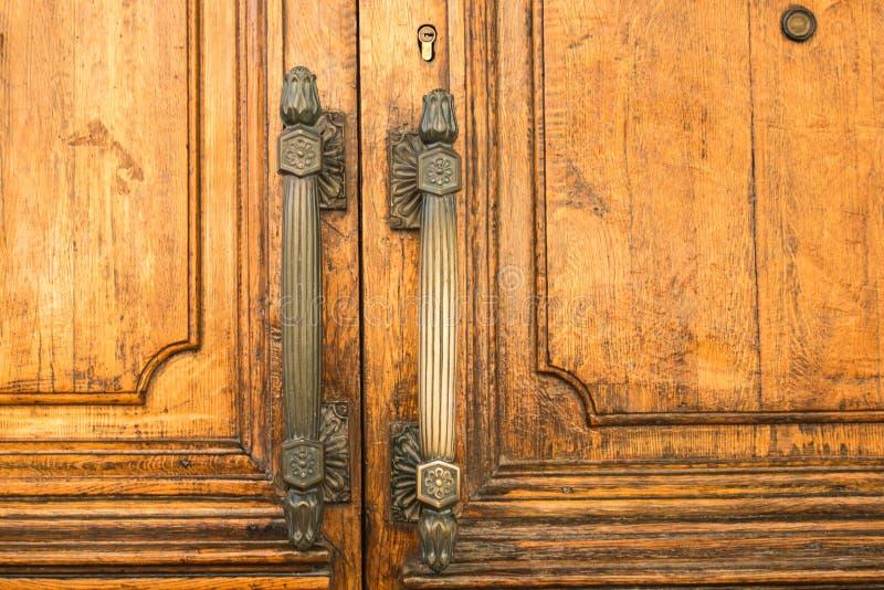 Massiva trädörrar med stora metallhandtag på det gamla byggnadsslutet royaltyfria bilder