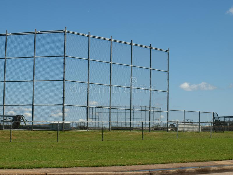 A Massive Athletic Field Area At a Dallas High School. An unusually high back stop on a ball diamond for safety reasons in a high-density living area surrounding stock images