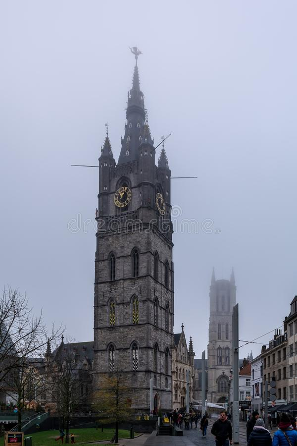 The massive Belfry of Ghent, topped by a dragon, against grey winter sky stock image