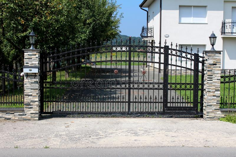 Massive black wrought iron entrance doors with decorations held in place by two stone poles with baroque style street lamps on top. And trees and family royalty free stock photography