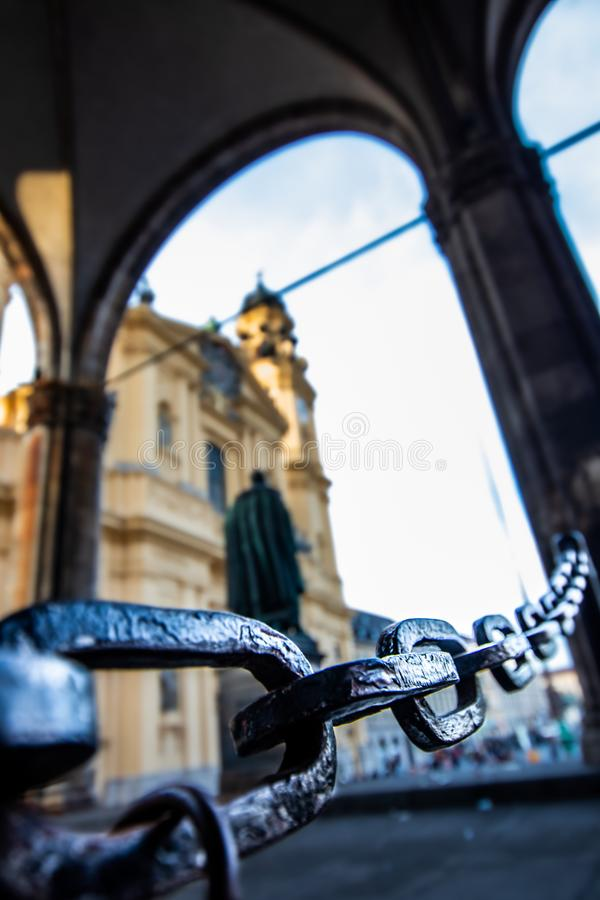 A massive chain of the feldherrenhalle odeonsplatz in munich with the theatine church in the background.  royalty free stock image