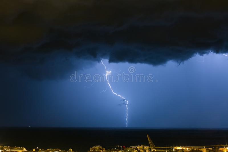 Massive cloud to ground lightning bolts hitting the horizon of city lights royalty free stock images