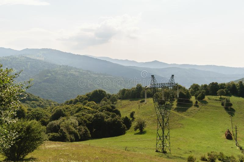 Massive electricity pole in nature, green vegetation covered mountains in background. high voltage electricity pillar royalty free stock images