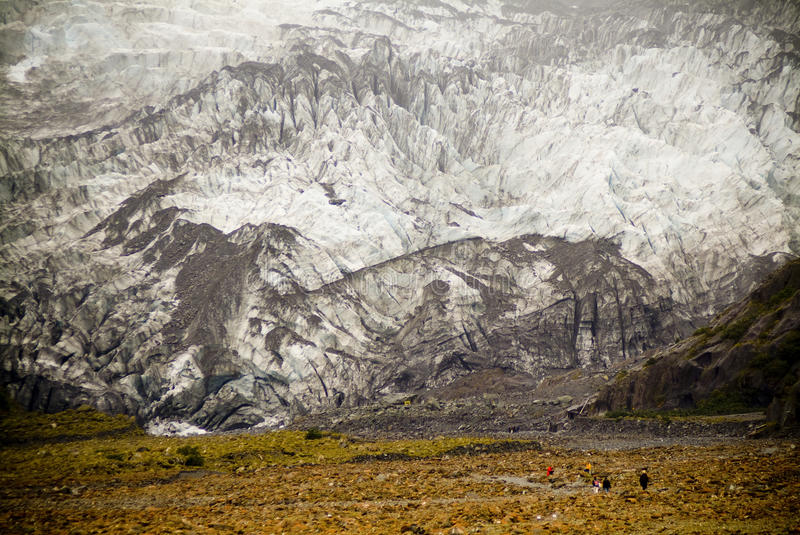 Massive Glacier. People walking in front of massive glacial wall stock image