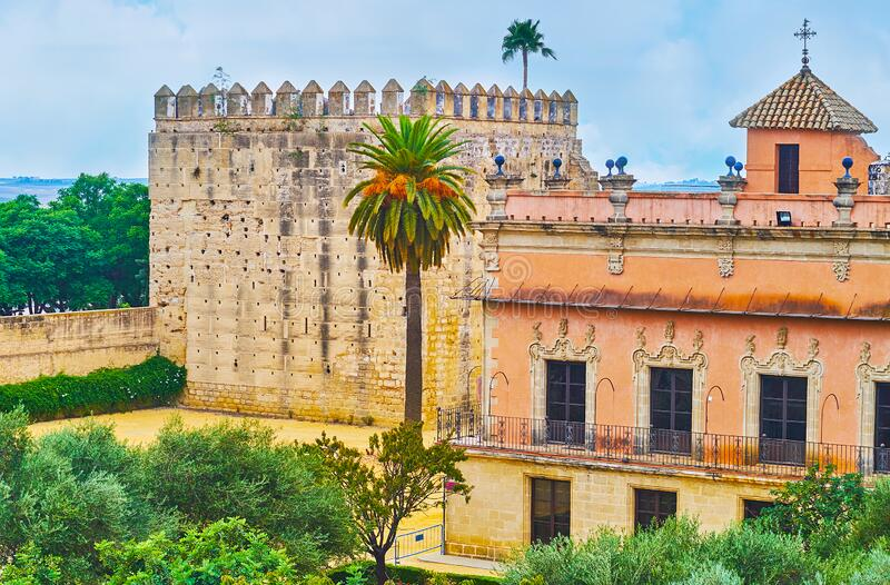 Visit Alcazar, Jerez, Spain. The massive Homage tower and ornate Villavicencio palace, surrounded by Alcazar garden, Jerez, Spain royalty free stock photography
