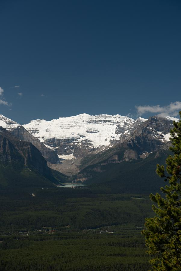 Mountain backdrop Lake Louise Alberta Canada. Massive mountains and glaciers are a backdrop to this vertical scenic of Lake Louise valley in Alberta Canada royalty free stock photo