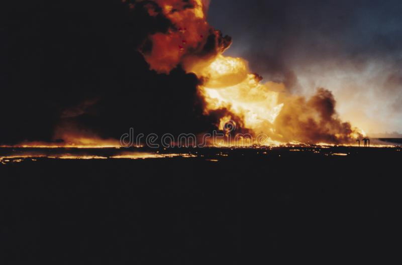 Massive oil well fire in field with oil slick, Kuwait. Burning oil well in field coated in spilled oil in aftermath of Operation Desert Storm, Persian Gulf War royalty free stock photos