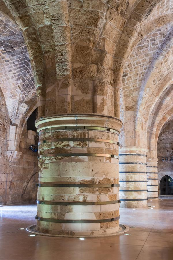 Massive pillars supporting the ceiling in the dining room in the ruins of the fortress in the old city of Acre in Israel stock images