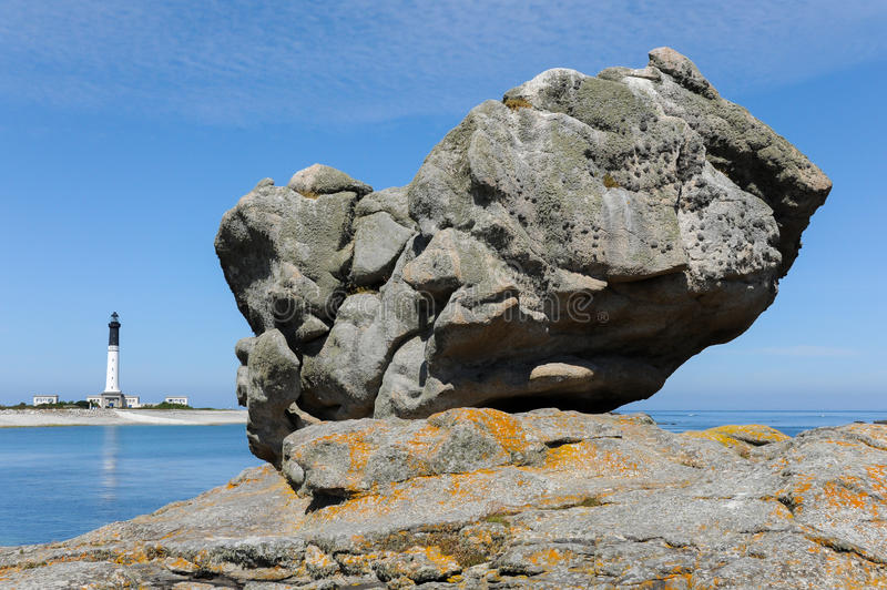 Massive rock on a beach on Ile de Sein with the lighthouse in t stock image