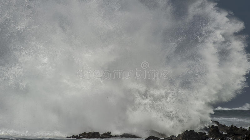 Massive Wave Brkes on Rocks. A massive wave explodes and disintergrates as it brakes on the shoreline stock photography