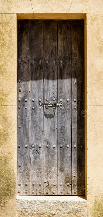 Massive wooden door with rivets in it`s frame of weathered stone royalty free stock photo