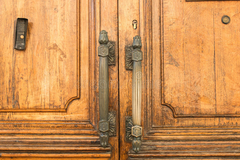 Massive wooden doors with large metal handles on the old building close. stock image