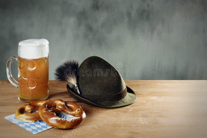 Masskrug啤酒、椒盐脆饼和帽子 免版税图库摄影