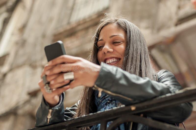 Massmedia för internet för lycklig flicka hållande ögonen på socialt i mobiltelefon royaltyfri bild