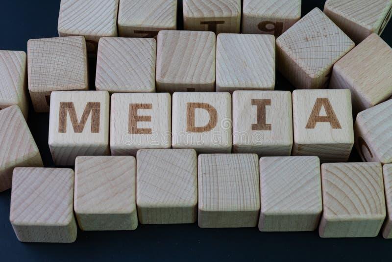 Massmedia, socialt massmedia press och nyheternabegrepp, kubträkvarter med alfabet att kombinera ordmassmedia på svart svart tavl royaltyfri foto