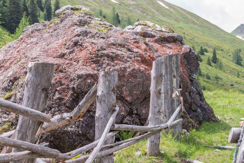 Masso di pietra gigante su un pascolo e su un recinto di legno distrutto, Austria immagini stock