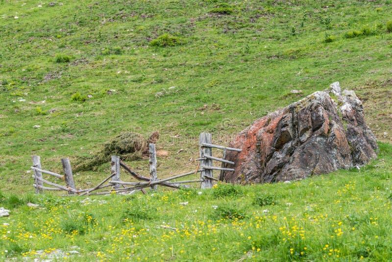 Masso di pietra gigante su un pascolo e su un recinto di legno distrutto, Austria fotografia stock