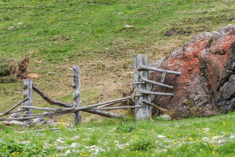 Masso di pietra gigante su un pascolo e su un recinto di legno distrutto, Austria immagine stock libera da diritti