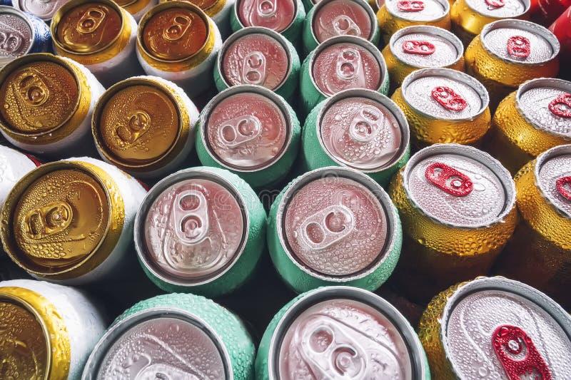 Massor av aluminiumburkar i isen i den öppna kylen Droppar av vatten på ett kallt kan av drinken Metall på burk av öl med iskuber royaltyfria foton