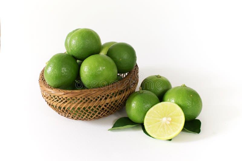 Massor av grön citron är i en träkorg Och någon av yttersidan med citronskivor som klipps i halva på sidan royaltyfri fotografi