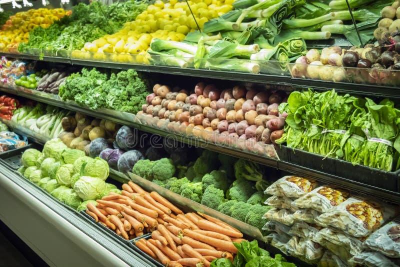 Massor av grönsaker i jordbruksproduktergången på en supermarket royaltyfri bild