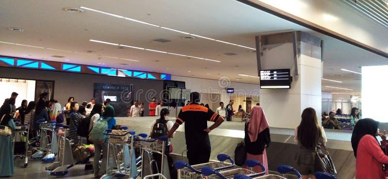 Massor av människor som får bagage på flygplatsen arkivbild