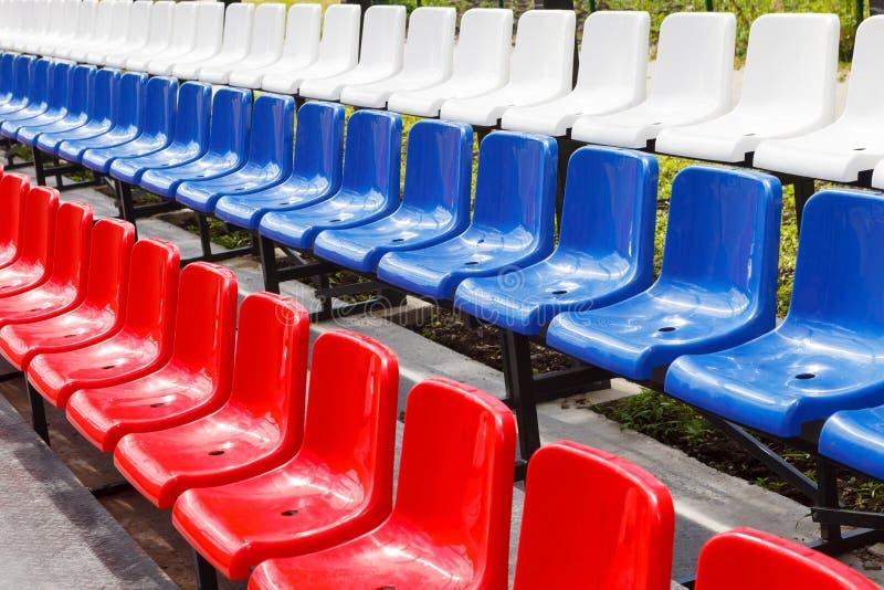 Massor av plast- stolar som är röda som är blåa och som är vita i stadion eller lekplatsen royaltyfria bilder