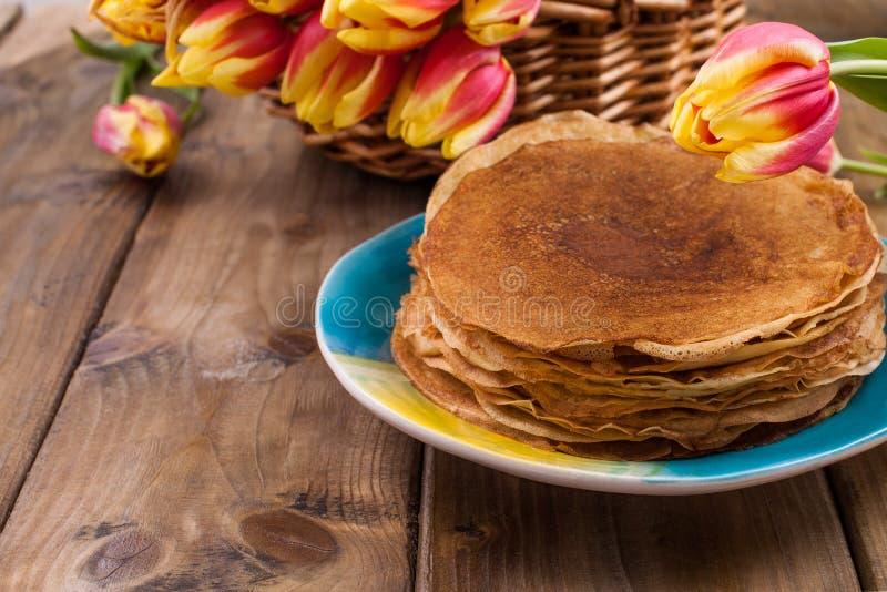 Massor av tunna pannkakor på en träbakgrund eller tabell och en korg med nya röd-guling tulpan Bakning är hem- för royaltyfri fotografi